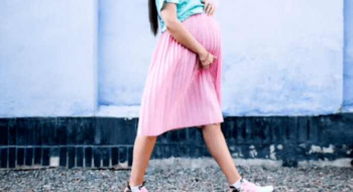 Picture of a pregnant woman wearing shoe walking on the road