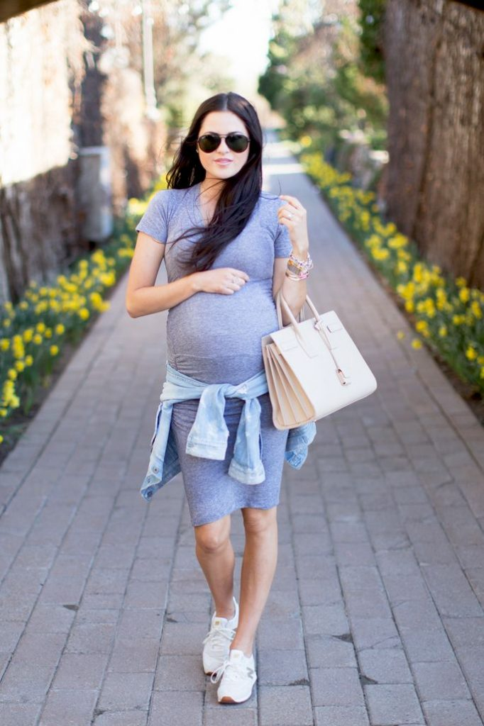 Picture of a pregnant woman walking on the road wearing blue dress wearing white shoes